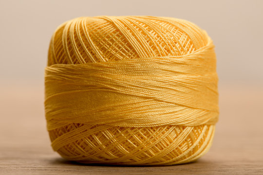 close up view of yellow cotton knitting yarn ball on beige