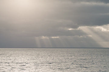 cloudy sky with sun rays in the open sea