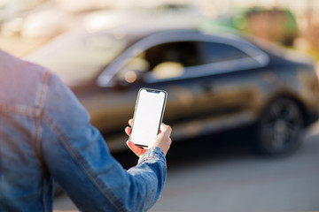 Young business man with phone in car. Man holding smartphone with blank screen .
