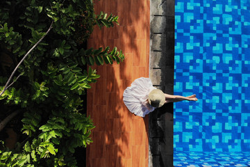 Top view of young woman in white dress and straw hat sitting near swimming pool. without face. Drone photo.Space for text