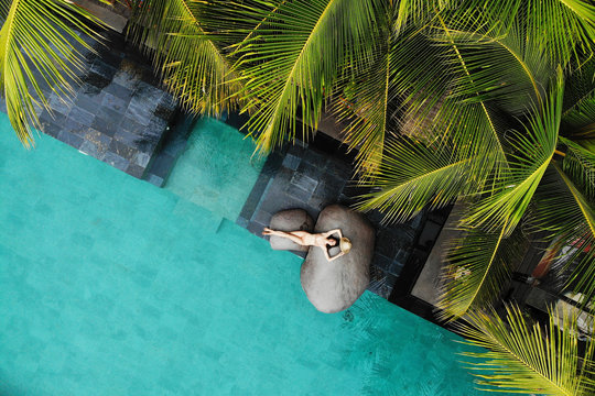 Top view of slim young woman in beige bikini and straw hat relaxing near luxury swimming pool and palm trees.Vacation concept. Drone photo