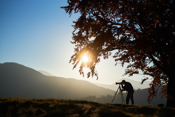 Tourist photographer using tripod and camera to take picture of mountain panorama at dusk and setting sun, standing under large oak tree on woody foggy mountains landscape and blue sky background.