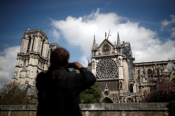 A man takes pictures of Notre-Dame Cathedral two days after a massive fire devastated large parts of the gothic structure in Paris