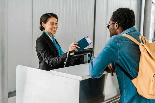 smiling african american airport worker giving passport and air ticket to tourist with backpack
