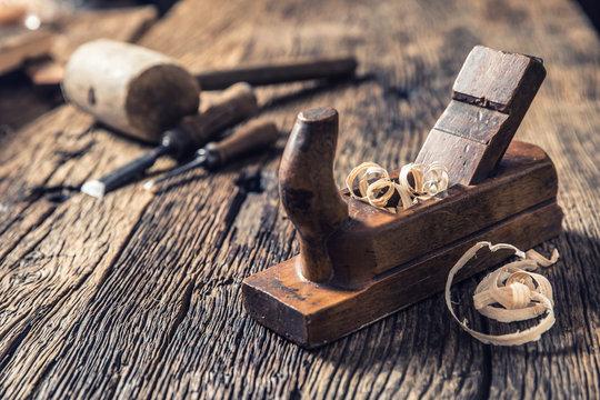 Old planer and other vintage carpenter tools in a carpentry workshop