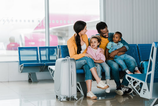 smiling african american family with baggage and kids sitting in airport