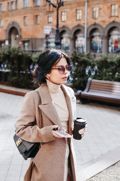 Stylish woman listning music on her airpods in city