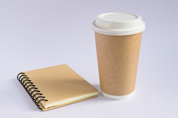 craft paper coffee cup and notebook diary with copy space on gray background in minimalism style