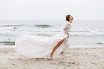 bride runs along the sea beach on a cloudy day