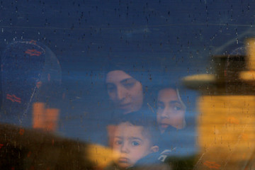 Wife and children of Palestinian prisoner Ayman Ghareeb, who is held in an Israeli jail, look out of a bus window on their way to visit him in the jail, in the Israeli-occupied West Bank