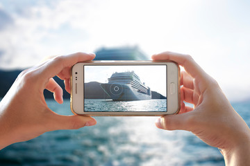 Photo camera of a smartphone. Young woman takes a photo of a cruiser.