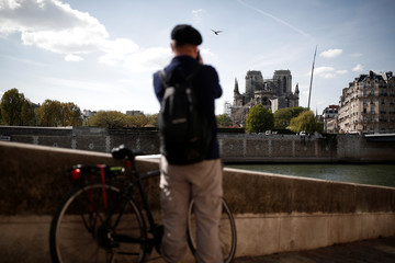 A man takes a picture of Notre-Dame Cathedral two days after a massive fire devastated large parts of the gothic structure in Paris