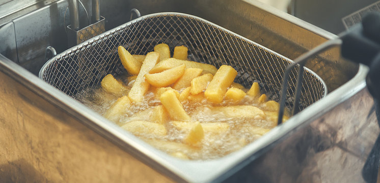 French fries cooking. Grid with strips of potato lowered into boiling oil. The concept of fast food. Belgian frit