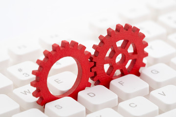 Two red gears on computer keyboard