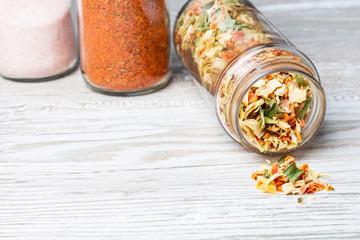 Przyprawy na kuchennym blacie. Liofilizowane warzywa wysypujące się ze słoika.