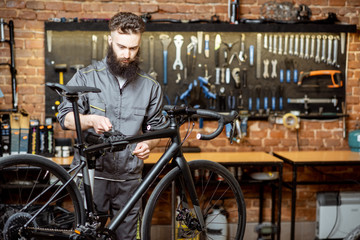 Handsome bearded repairman in workwear serving a sports bike at the bicycle workshop