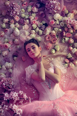 Keep loving. Top view of beautiful young woman in pink ballet tutu surrounded by flowers. Spring mood and tenderness in coral light. Art photo. Concept of spring, blossom and nature's awakening.