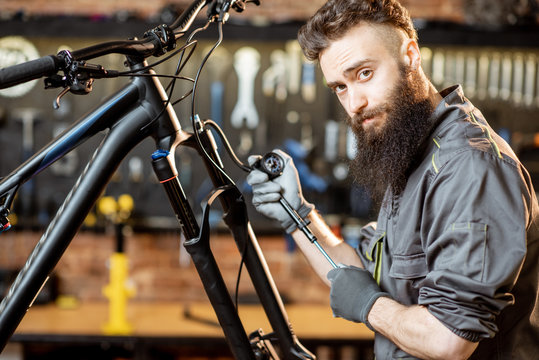 Repairman pumping shock absorber of the mountain bike in the workshop of the bicycle shop