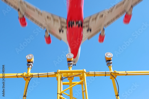 airplane flying above airport runway approach lights against
