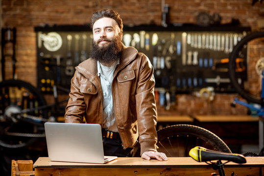 Portrait of a handsome bearded man as bicycle store owner or manager standing with laptop at the bicycle workshop