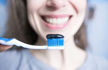 Toothpaste and brush of black activated carbon. Charcoal in the hands of a woman.