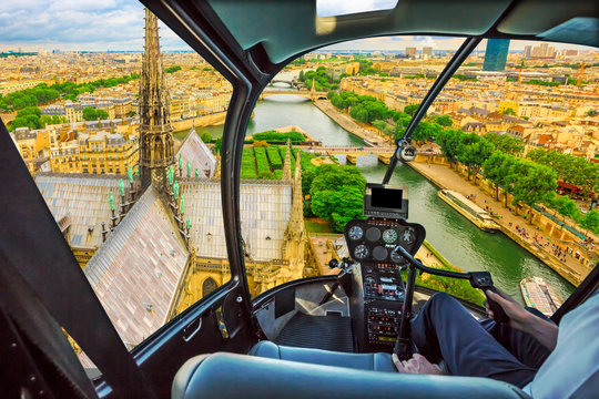Helicopter flying on the roof of Notre Dame church spotting its spire, in Paris panorama, French capital, Europe. Scenic flight over Paris cityscape.
