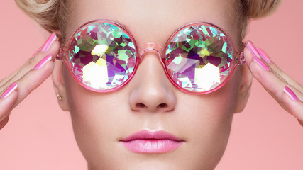 Obraz Portrait of Beautiful young Woman with Colored Glasses. Beauty Fashion. Perfect Make-up. Pink Nails Manicured. Colorful Decoration. Holographic sunglasses. Coral color - fototapety do salonu