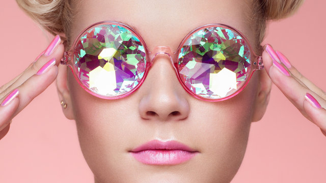 Portrait of Beautiful young Woman with Colored Glasses. Beauty Fashion. Perfect Make-up. Pink Nails Manicured. Colorful Decoration. Holographic sunglasses. Coral color