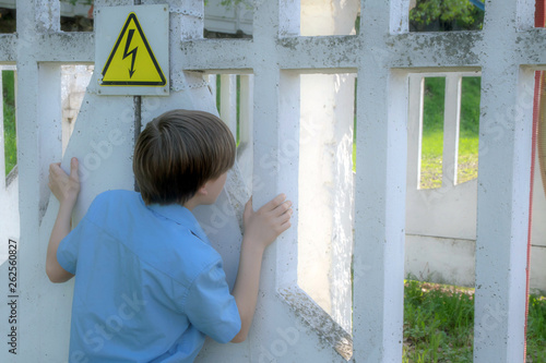 naughty teen looks behind a sign of electrical danger near a fenced