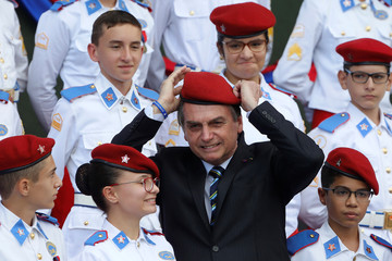 Brazil's President Jair Bolsonaro poses for a picture with students of the military college during an Army Day ceremony, in Brasilia