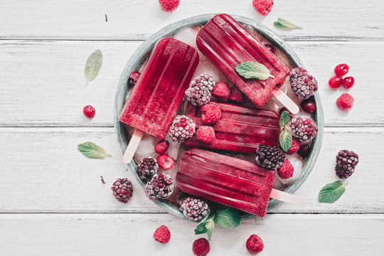 Homemade berry popsicles decorated berries and mint leaves on a white rustic wooden plank. Overhead view,flat lay