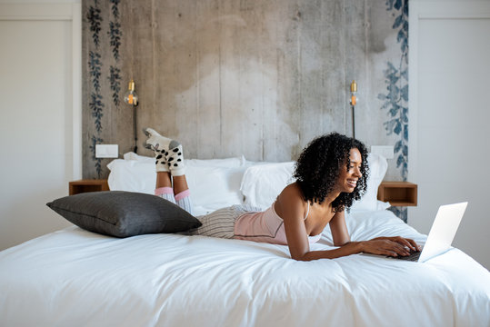 Woman sitting on bed on the computer