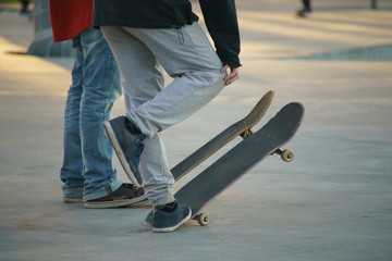 Image of skateboarders' legs and skate.