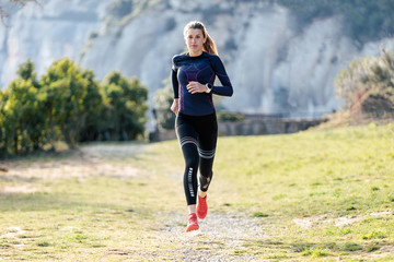 Fototapeta Sporty young woman running on mountain in beautiful nature. obraz