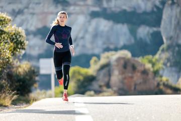 Fototapeta Sporty young woman running on mountain road in beautiful nature. obraz