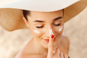 Beautiful Young woman with sun cream on face. Girl holding sunscreen bottle on the beach. Female in hat applying  moisturizing lotion on skin.Skin care. Sun protection. Suntan