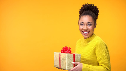 Joyful afro-american female holding present on bright background, happiness Fototapete