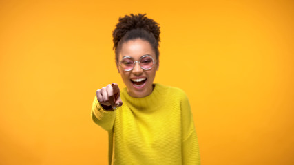 Laughing young female pointing finger in camera, having fun, joking, positivity