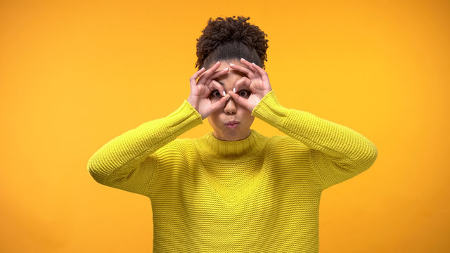 Smiling black woman making faces on yellow background, having fun, youth humor