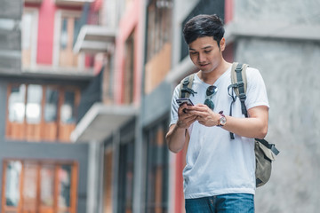 Traveler Asian man direction on location map in Beijing, China, backpacker male using mobile phone looking on map find landmark while holiday trip. Lifestyle men travel in city concept