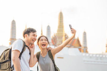 Asian blogger couple travel in Bangkok, Thailand, sweet couple using mobile phone selfie and photo view while spending sweet time in holiday trip in sunset. Couple travel in city concept.