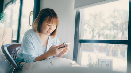 Business freelance Asian woman using smartphone for talking, reading and texting while sitting on table in cafe. Lifestyle smart beautiful women working at coffee shop concepts.