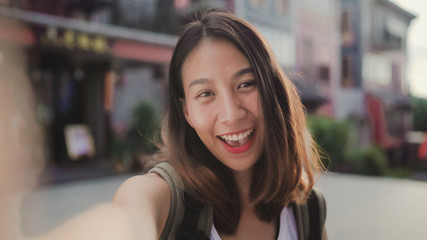 Cheerful beautiful young Asian backpacker blogger woman using smartphone taking selfie while traveling at Chinatown in Beijing, China. Lifestyle backpack tourist travel holiday concept. Point of view.