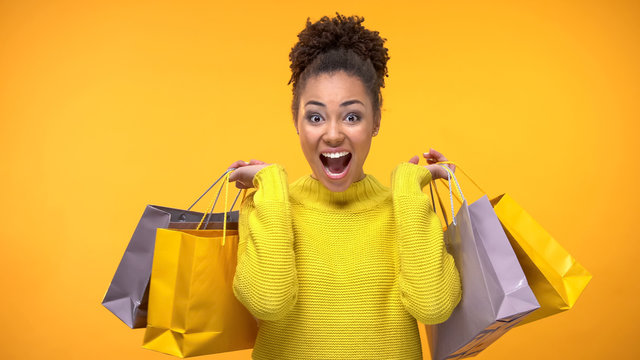 Happy african-american woman shopping bags, seasonal discount, holidays sale