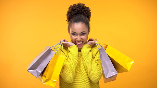 Excited young woman in stylish yellow sweater holding shopping bags, discount