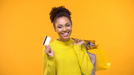 Stylish young female with purchase bags showing credit card, shopping cash back