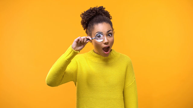 Curious afro-american woman looking magnifying glass, having fun, surprise