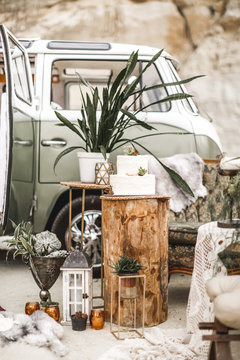 Stylish rustic decor composition of the vintage sofa, golden iron decorations with cactus succulents and plants, candles and wedding cake on wooden log. Rustic wedding decor and hippy bus