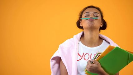 Positive african teenager holding pencil between nose and lips, mustache joke