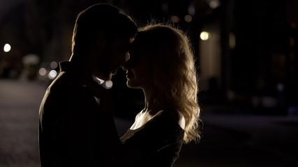 Silhouettes of husband and wife nuzzling, romantic date, love relationship